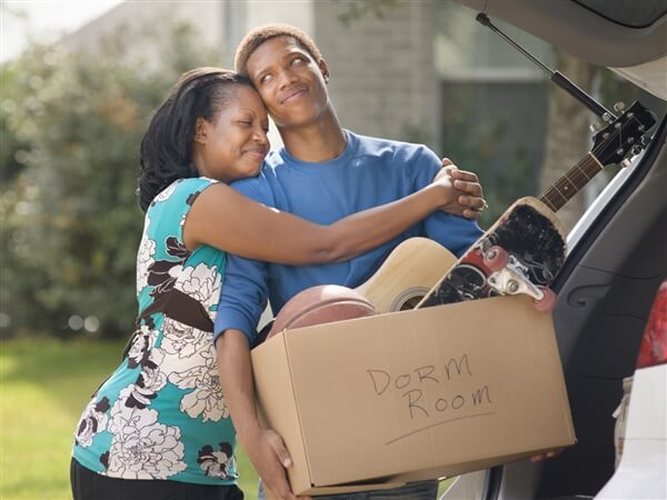 Mother hugging son moving into college dorm